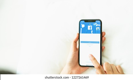 Bangkok, Thailand - November 12, 2018 : hand is pressing the Facebook screen on apple iphone 6 ,Social media are using for information sharing and networking.