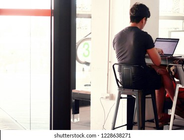 Bangkok /Thailand - November 13, 2018  A young Thai man working with laptop in co-working space cafe in shopping mall.