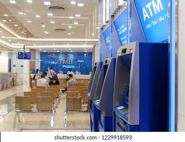 Bangkok /Thailand - November 13, 2018 : Thai TMB retail banking customer service, comparing the human service at branch counter inside the bank versus automatic self service outside.