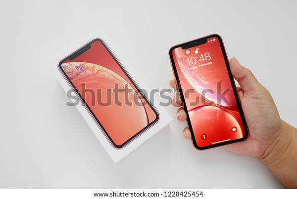 Bangkok, THAILAND - NOVEMBER 13, 2018:woman hand holds Coral Apple iPhone Xr with package on white background ,top view