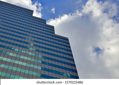 Bangkok, Thailand - November 16, 2019 : Angle view from below, Looking up CAT telecom tower in Cloud sky, Modern glass window of building reflection with blue sky and white clouds.