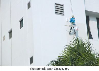 BANGKOK, THAILAND - NOVEMBER 17,2018 : Worker painting color on building wall with roller brush on 17 November 2018 in Bangkok,Thailand.
