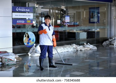 Bangkok, Thailand - November 18, 2011: A cleaner sweeps water at Don Mueang International Airport as Thailand deals with its worst flooding in decades.