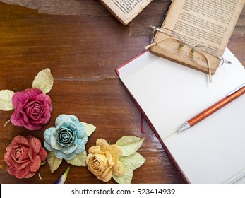 BANGKOK, THAILAND - NOVEMBER 18, 2016: Artificial roses, notebook, books, pen and glasses on wooden table for writing some article.