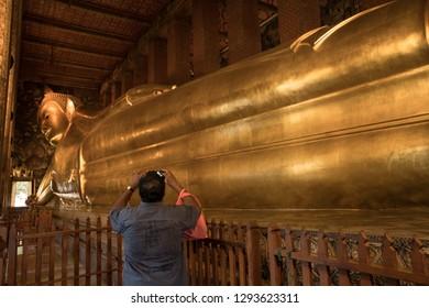 Bangkok, Thailand - November 19, 2018: Tourist takes a photograph of the reclinning buddha at Wat Pho