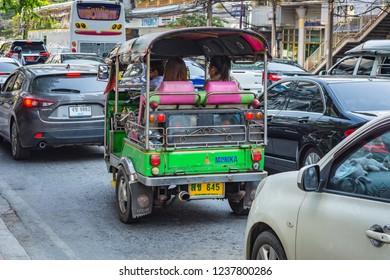 BANGKOK, THAILAND - NOVEMBER 2018: Auto rickshaw (tuk-tuk) with passengers on the street in the sunny day in Bangkok, Thailand