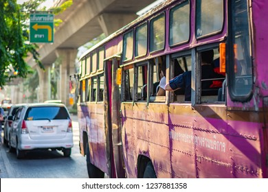 BANGKOK, THAILAND - NOVEMBER 2018: Pink bus with passengers is going on the street while the sunset in Bangkok, Thailand