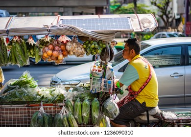 BANGKOK, THAILAND - NOVEMBER 2018: Salesman is riding on his bike with fresh vegetables and fruits in Bangkok, Thailand