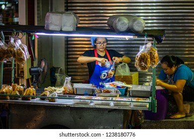 BANGKOK, THAILAND - NOVEMBER 2018: Street food in Bangkok in the evening, woman is packing food, other woman is washing dishes, Thailand