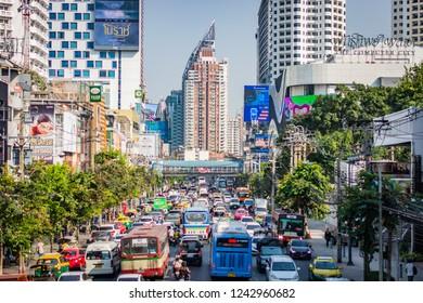 BANGKOK, THAILAND - NOVEMBER 2018: Street in Bangkok (Thailand), a big traffic jam, a lot of cars and buses, a sunny day, buildings, trees