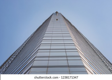 BANGKOK, THAILAND - NOVEMBER 2018: Tall building with blue glass windows in Bangkok, Thailand, view and perspective from the ground, blue sky above