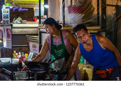 BANGKOK, THAILAND - NOVEMBER 2018: Thai muslim couple are preparing and cooking thai food in the evening on the night market
