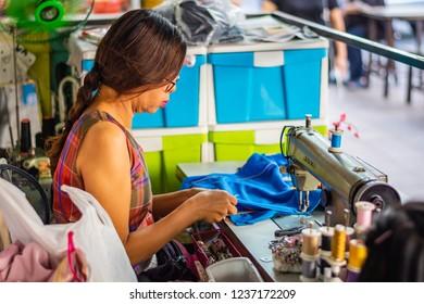 BANGKOK, THAILAND - NOVEMBER 2018: Woman sewing on a sewing machine running a tailor shop on a street in Bangkok, Thailand
