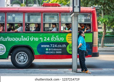 BANGKOK, THAILAND - NOVEMBER 2018: Woman standing on the street leaning against a pole, a red bus with people inside runs in the background in Bangkok, Thailand