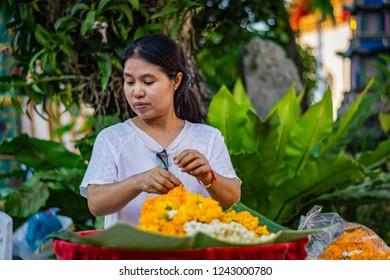 BANGKOK, THAILAND - NOVEMBER 2018: Woman florist arranges orange flowers at the Buddhist temple of Wat Pho in Bangkok, Thailand