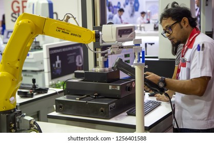 Bangkok, Thailand - November 21, 2018: Worker control robot arm to loading and unloading workpiece in Metalex 2018