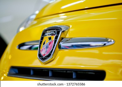 BANGKOK, THAILAND - November 21, 2018: The front view of yellow Fiat 500 Abarth logo hood, and bumper with shiny paint with reflection on bonnet after polishing. High performance road car concept.
