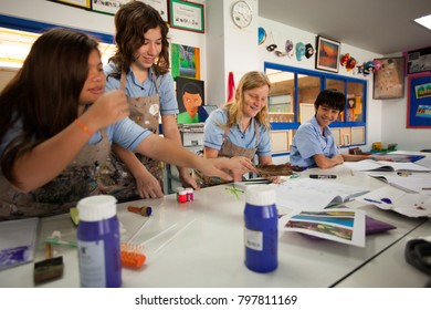 BANGKOK, THAILAND - NOVEMBER 23, 2012: In a college in Bangkok, students in uniform, have fun painting during a course of art and painting.