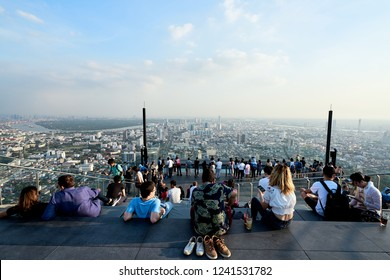 BANGKOK - THAILAND, November 24, 2018:Group of people or travelers enjoying and overlook a cityscape at rooftop bar of high building called Mahanakhon Skywalk in Bangkok Thailand