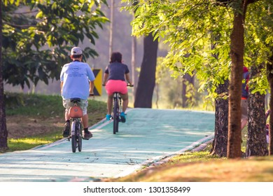 BANGKOK, THAILAND - November 25, 2018 : People riding bicycles in bike lanes at Vachirabenjatas Park. / Take bicycle in bicycle track in park for exercise.