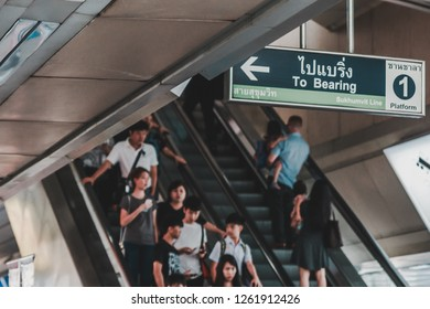 Bangkok, Thailand - November 26, 2016: Commuters using the escalator to reach the platform floor of Siam BTS Skytrain Station in the middle of the day on weekend with direction sign overhead