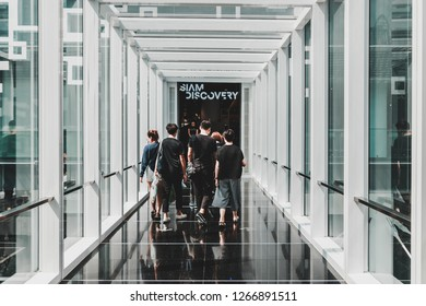 Bangkok, Thailand - November 26, 2016: Interior of modern glass walkway connecting Siam Center to Siam Discovery in Siam Square District. Group of teenager is walking through.