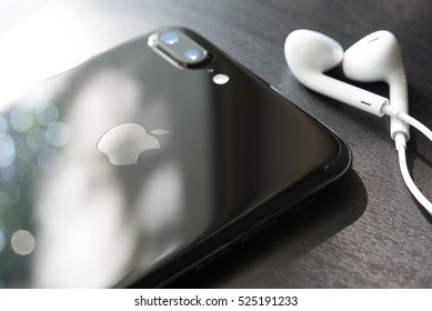 BANGKOK, THAILAND - NOVEMBER 26, 2016: Iphone7 Plus jet black series face down on floor with ear phone, Apple inc new smartphone