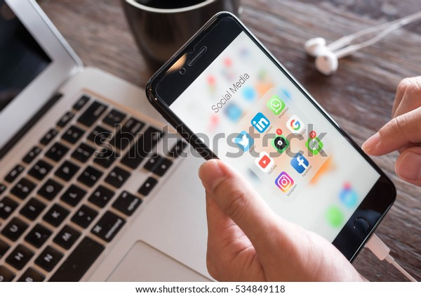 BANGKOK, THAILAND - NOVEMBER 26, 2016: Man using Iphone7 Plus jet black serie with application icons of social media on screen