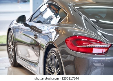 BANGKOK, THAILAND - NOVEMBER 26, 2018: The shiny  Porsche Cayman S sports car with gray paint & tail light detail after ceramic coat. Concept of car detailing & paint protection. Side shot from behind