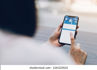 Bangkok, Thailand - November 27, 2018 : hand is pressing the Facebook screen on apple iphone x ,Social media are using for information sharing and networking.
