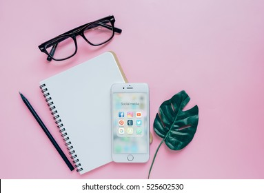 BANGKOK, THAILAND - NOVEMBER 28, 2016:  Group of Popular Social network icons showing on Apple iPhone 6s screen with notebook and eyeglasses, Social media are popular tool for communication.