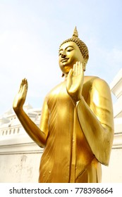 BANGKOK, THAILAND - NOVEMBER 28,2017:Photo of Golden standing Buddha statue on clear sky background in Pariwas Temple, Bangkok Thailand.