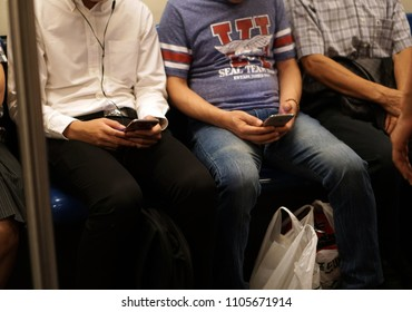 Bangkok Thailand - November 29, 2017: The passenger hand using mobile phone devices to kill time inside MRT subway train, Smartphone addiction lifestyle daily, Social technology telecommunication