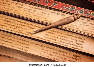 Bangkok, Thailand - November 8, 2018 : pen for writing text on Bai Lan background, Bai Lan or ancient palm leaf manuscripts content about buddhist scriptures, Pali language Khmer