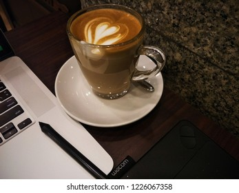 Bangkok, Thailand – November 9,2018 : Top down view of Macbook and Wacom tablet with coffee cup on wood table in coffee shop.