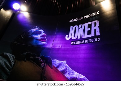 Bangkok, Thailand - Oct 1, 2019: Joker movie backdrop poster with spotlights showing in movie theatre. Cinema promotional advertisement, or film industry marketing concept