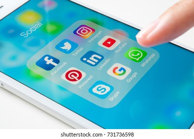 Bangkok, Thailand - OCT 11, 2017: Hand using white Iphone7 with icon social media on screen smartphone marketing communication business and technology background digital share network app editorial