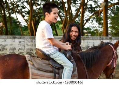 Bangkok, Thailand - Oct 11, 2018:  A child with special needs is riding with a close supervision teacher. This is a treatment called Hippo therapy.