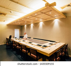 BANGKOK, THAILAND. OCT 12, 2016: Japanese Omakase Restaurant that decorated mostly with wood. Chef cooking in kitchen counter and directly serve to customer.