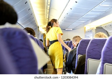 Bangkok Thailand, Oct 15 ,2018 , Airline nokscoot Interior of airplane with passengers on seats and stewardess in Yellow uniform at the aisle.