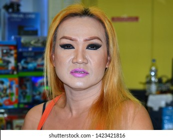 BANGKOK, THAILAND - OCT 16, 2015: Young Thai genderqueer salesperson with pink lipstick, thick eye make-up and long blonde hair poses for the camera, on Oct 16, 2015.