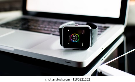 Bangkok, Thailand - Oct 2018: Close up of wrist watches with icons and Gray Aluminum Case, Black Sport Band, Laptop, smartphone. Black fitness watch (activity tracker) on iPhone 6 with Macbook pro