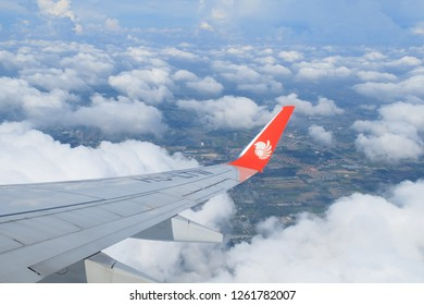 BANGKOK, THAILAND - OCT 5, 2018 :Cloud and blue sky under the aircraft  Boeing 737-900ER (HS-LTW) with the Lion air logo sign on right winglet.