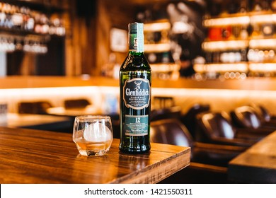 BANGKOK, THAILAND. OCT 7, 2016: Single malt Scotch whisky in green glass bottle with whiskey and sphere ice in drinking glass on wooden table with warm and cozy lights in background.