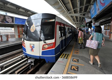 BANGKOK, THAILAND - OCT 8, 2013: Rail travellers wait for an approaching BTS Skytrain at a city centre station. The Thai capital's BTS rail public transport system serves 600,000 passengers daily.