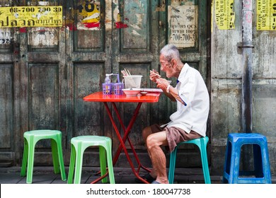 BANGKOK, THAILAND - OCTOBER 04: Unidentified man eats on a street in chinatown district, Bangkok, Thailand on October 04, 2012. Chinatown is renowned for its street food and outdoor dining.