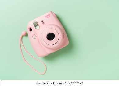 BANGKOK, THAILAND - OCTOBER 09, 2019: The pink Fujifilm Instax mini 8 instant camera on green background.