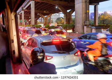 BANGKOK, THAILAND - October 1: Ladprao intersection on October 1,2018 in Bangkok, Thailand. People drive car and motorcycle in the rian with traffic jam at Ladprao intersection.