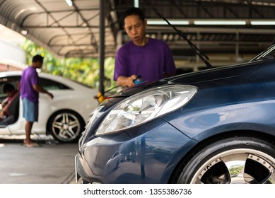 Bangkok, Thailand - October 10, 2018 : Unidentified car care staff cleaning (clean, wash, polish and wax) the car (Car detailing) at car care shop in Bangkok Thailand