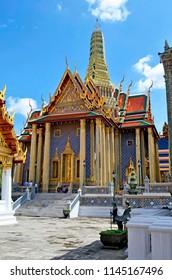 Bangkok, Thailand - October 11, 2014: Visitors resting in the shadow of the Prasat Phra Thep Bidon at the Wat Phra Kaew in the Grand Palace enclosure.